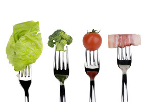 Fresh raw vegetable and meat food on forks over white background